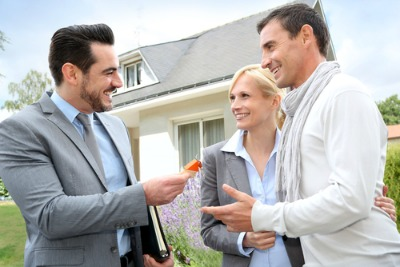 Real estate agent handing keys to a man and woman for their new home