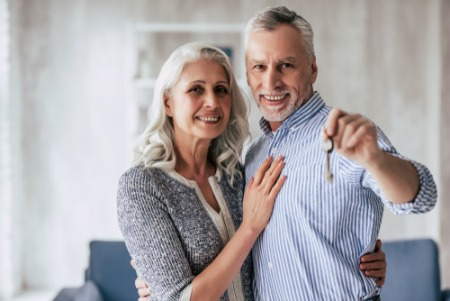 Smiling older couple holding keys after buying a home