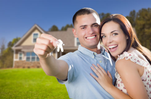 Young couple holding house keys to their new home