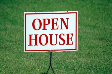 Open house sign on green grass